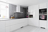 Simple white kitchen with grey worksurfaces and grey back wall