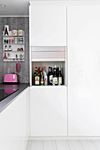 Simple white kitchen with miniature bar in roller-fronted cupboard