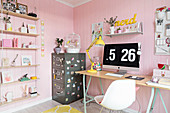 Desk and metal filing cabinet in feminine room with pink walls