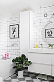 White bathroom with subway wall tiles and simple modern furnishings