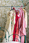 Women's clothing hung from metal frame of ornate four-poster bed