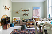 Antlers on pastel-green walls of Bohemian-style living room