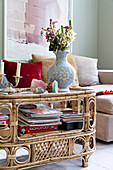 Magazines, games and vase of flowers on vintage-style rattan table in front of sofa