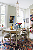 Stylish, white, oval dining table and upholstered chairs in period apartment