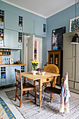 Pale blue cupboards and rustic wooden dining table in Bohemian-style kitchen