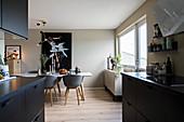 Offene Küche mit schwarzen Fronten und Esszimmer in Erdfarben