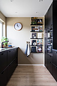 Black cabinets and books on ledges in kitchen