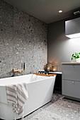 Free-standing bathtub in grey modern bathroom