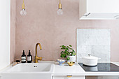 White fitted kitchen with powder-pink wall