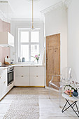 White fitted kitchen with stucco ceiling, board floor, side table and classic chair