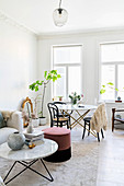 Couch, coffee table and pouffe in front of dining area in white interior with stucco ceiling
