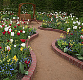 Garden swing amongst beds of multicoloured tulips
