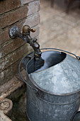 Watering can under ornate garden tap