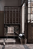 Delicate chair in front of old, industrial, metal door