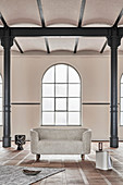 Modern, oval sofa in old factory building with metal pillars