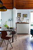 Dining table with black and gold pendant lamps below arched wooden ceiling