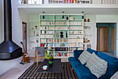 Velvet sofa, suspended fireplace and bookcase in living area of maisonette apartment