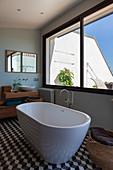 Modern, free-standing bathtub and hexagonal floor tiles in bathroom