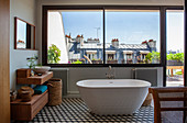 Large window, free-standing bathtub and hexagonal floor tiles in bathroom