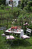 Set garden table with folding chairs in summery cottage garden