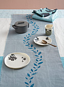 Tablecloth runner printed with leafy tendril on simply set table