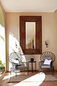 Two modern metal chairs below Oriental mirror on wall