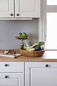 Rustic wooden bowl and vegetables on silver cake stand in kitchen