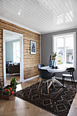Wooden wall in dining room with open doorway leading into living room