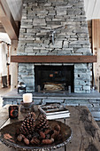 Open fireplace with stone surround in rustic living room
