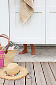 Raffia basket and sun hat; woman's feet below saloon door