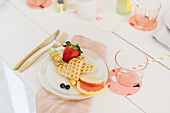 Waffles with fruit and cream on festively set table