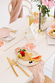 Waffles and fruit on table festively set in delicate pink shades
