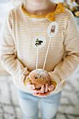 Kind hält mit Papiersteckern dekorierten Muffin in den Händen