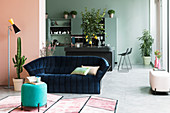 Dark blue velvet sofa in loft apartment with walls in pastel tones