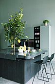 Charcoal-grey island counter with lemon tree planted in centre and bar stools in open-plan kitchen