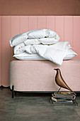 Feather pillows on pink ottoman