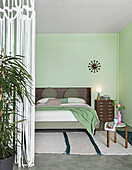 Double bed and pale green walls in sleeping area separated by string curtain in loft apartment