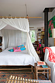 Bed with canopy in bedroom with topical ambience