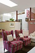Pink gestreifte Sessel im offenen Wohnraum auf mehreren Ebenen