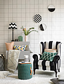 Graphic design: black-and-white striped armchair, stool, shelves, cushions, decorative wall plates and tile-effect wallpaper