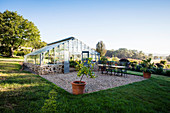 Lemon trees and table and chairs on gravel yard in front of greenhouse
