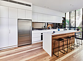 Large, modern kitchen with wooden floor, island counter and glass wall