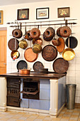 Collection of old pans and cake tins on wall above old wood-fired stove in kitchen