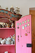 Crockery in farmhouse cupboard with religious pictures on inside of open door