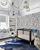 Nursery with rabbit wallpaper, blue cowhide rug, crib and dramatic glass ball chandelier