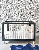 Crib, rabbit wallpaper and blue cowhide rug in nursery
