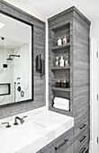 Grey wood washstand with built in shelves, black sconce lamp and mirror on wall