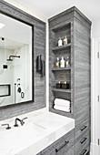 Graue Badmöbel mit eingebauten Regalen aus Holz, schwarze Wandleuchte und Wandspiegel