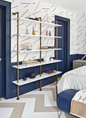White shelving with brass frame against blue wainscoting in bedroom