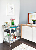 Chrome and glass bar trolley beside sideboard